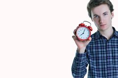 Close-up portrait of a troubled young man holding alarm clock isolated over white background. Late for work, bad sleep. Place for text or image stock photography