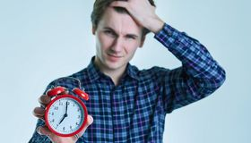 Close-up portrait of a troubled young man holding alarm clock isolated over white background. Late for work, bad sleep. Place for text or image royalty free stock image
