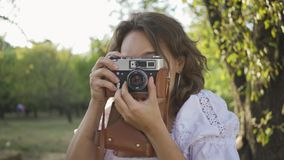 Portrait of attractive young photographer with curly hair looking at the camera while taking photo using old camera in. Close-up portrait of ttractive young stock video footage