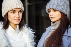 Close up portrait of two beautiful friends young women in autumn, winter clothes wearing posing on gray background. Close up portrait of two beautiful friends Royalty Free Stock Photography