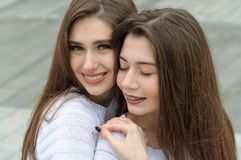 Close-up portrait of two brunettes. They both have long brown hair that is long to the waist and they are dressed in identical white sweaters Royalty Free Stock Photos