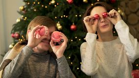 Close up portrait of two cheerful, positive couple holding round glossy toys, covering eyes, fooling around on decorated royalty free stock photos