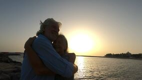Close up and portrait of two happy and active seniors or pensioners having fun and enjoying looking at the sunset smiling with the