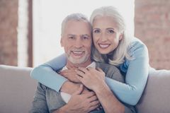 Close up portrait of two happy old married people, they are hugging and have perfect shiny white smiles royalty free stock images