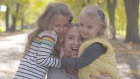 Close-up portrait of two joyful caucasian little sisters hugging curly blond woman in the autumn park. Cute smiling