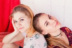 Portrait of two pretty girls sitting in a pose back to back Royalty Free Stock Photos