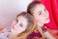Portrait of two pretty girls sitting in a pose back to back Stock Images