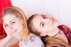 Portrait of two pretty girls sitting in a pose back to back Royalty Free Stock Photo