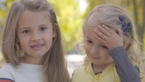 Close-up portrait of two pretty little caucasian sisters standing in the autumn park and smiling. Beautiful smiling stock video