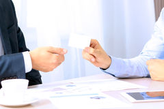 Close-up portrait of two successful business executive exchanging business card Stock Photos