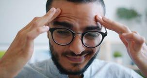 Close-up portrait of unhappy Arab in glasses touching head feeling headache. Close-up portrait of unhappy young Arab in glasses touching head feeling headache stock video
