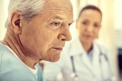 Close up portrait of unhappy retired gentleman at hospital stock photo