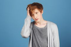 Close up portrait of unhappy young charming ginger male student in casual clothes holding hair with hand, looking aside Royalty Free Stock Image