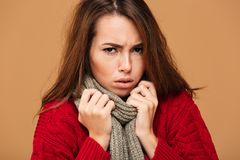 Close-up portrait of upset freezing woman in red knitted sweater. And gray scarf, looking at camera,  on beige background Royalty Free Stock Image