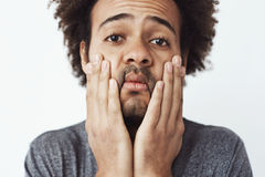 Close up portrait of upset and tired young african man grabing his face and cheeks with hands over white background Royalty Free Stock Photography