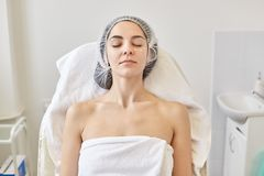 Close up portrait of well kept beautiful woman laying on coach with closed eyes, having peaceful facial expression, being naked,. Rolled with white towel and royalty free stock photo