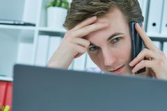 Close-up portrait of white collar talking to customer on mobile phone in office at workplace by laptop. Stock Photos