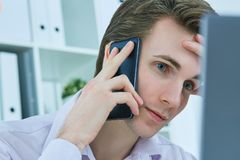 Close-up portrait of white collar talking to customer on mobile phone in office at workplace by laptop. Stock Image
