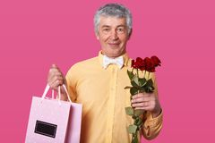 Close up portrait of white haired elderly man in yellow shirt and white bow tie, holds red roses and bags with present, being in stock image