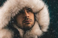 Close up portrait of a white man dressed with an eskimo jacket in the snow. Looking up royalty free stock photography
