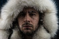 Close up portrait of a white man dressed with an eskimo jacket in the snow. Looking at the camera royalty free stock photography