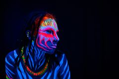 Close-up Portrait of Wild and frantic Young naked bodyarted woman in blue glowing ultraviolet paint and Yellow eye. Lenses. Avatar entity amazon warrior girl royalty free stock image