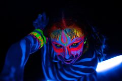 Close-up Portrait of Wild and frantic Young naked bodyarted woman in blue glowing ultraviolet paint and Yellow eye. Lenses. Avatar entity amazon warrior girl stock photos