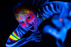 Close-up Portrait of Wild and frantic Young naked bodyarted woman in blue glowing ultraviolet paint and Yellow eye. Lenses. Avatar entity amazon warrior girl stock photography