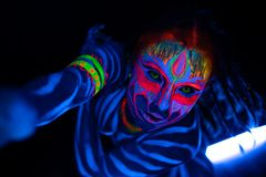 Close-up Portrait of Wild and frantic Young naked bodyarted woman in blue glowing ultraviolet paint and Yellow eye. Lenses. Avatar entity amazon warrior girl stock photo