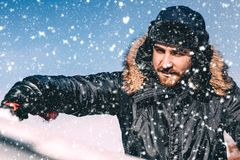 Close up portrait of winter concept - man cleaning car from snow, wearing hat and warm jacket royalty free stock image