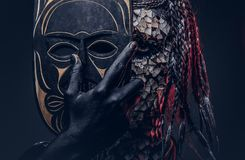 Close-up portrait of a witch from the indigenous African tribe, wearing traditional costume. Make-up concept. Isolated on a dark background royalty free stock photo