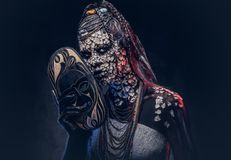 Make-up concept. Portrait of a scary African shaman female with a petrified cracked skin and dreadlocks, holds a. Close-up portrait of a witch from the Royalty Free Stock Images