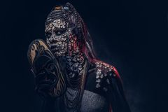 Make-up concept. Portrait of a scary African shaman female with a petrified cracked skin and dreadlocks, holds a. Close-up portrait of a witch from the Stock Photo