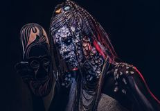 Make-up concept. Portrait of a scary African shaman female with a petrified cracked skin and dreadlocks, holds a. Close-up portrait of a witch from the Stock Image