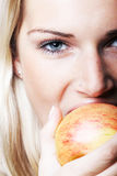 Close-up portrait of a woman bitting an apple Royalty Free Stock Image