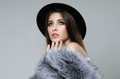 Close-up portrait of a woman in a black hat and fur. Which she holds in her hand. The model is dressed in a striped shirt, her shoulder is bare Royalty Free Stock Photography