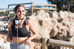 Close up portrait of a woman doing sport resting outdoor smiling and listening music Royalty Free Stock Photos