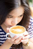 Close up portrait of woman drinking  cappuccino coffee Stock Image