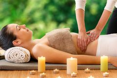 Woman having aromatic oil massage in outdoor spa. Royalty Free Stock Image