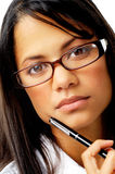 Close-up portrait of a woman in glasses. Expressionless woman holding a pen to her face with nerdy spectacles Royalty Free Stock Photo