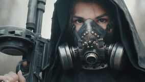 Close-up portrait of woman in grunge clothes hooded mantle and gas mask standing in forest and looking into camera