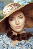 Close-up portrait of woman in hat. Close-up portrait of a beautiful young woman with braid hairdo in the hat, looking at camera, outdoors Stock Images