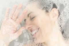 Close-up portrait of a woman having fun touching the glass in the shower Royalty Free Stock Photography
