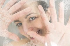 Close-up portrait of a woman having fun touching the glass in the shower. A Close-up portrait of a woman having fun touching the glass in the shower Stock Photos