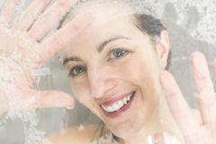 Close-up portrait of a woman having fun touching the glass in the shower. A Close-up portrait of a woman having fun touching the glass in the shower Royalty Free Stock Image