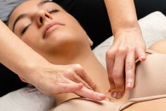 Chiropractor manipulating neuro lymphatic points on female chest. Close up portrait of woman having kinesiological therapy. Hands applying pressure on chest royalty free stock photography