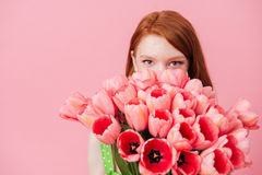 Close up portrait of woman hiding behind bouquet of flowers Royalty Free Stock Images