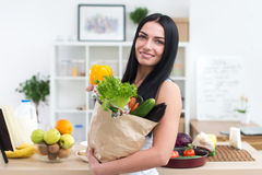 Close-up portrait of a woman holding paper bag full fresh vegetables. Happy smiling female vegetarian with grocery. Royalty Free Stock Image