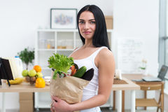 Close-up portrait of a woman holding paper bag full fresh vegetables. Happy smiling female vegetarian with grocery. Stock Images