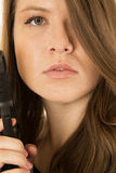 Close-up portrait of a woman holding a pistol with a serious exp Stock Photo